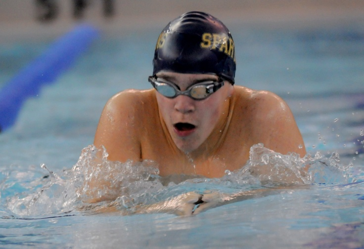 Max Gibbs, 9, takes a breath during a 100 meter breaststroke race. Photo by Scott Davis.