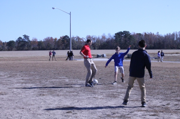 Upper school science teacher Chris Mitchell plays soccer with Thomas Sutton, 8, during lunch.