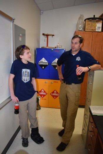 Ninth grader William Sutton and upper school teacher Chris Mitchell discuss Sutton's first place costume on Teacher Day.